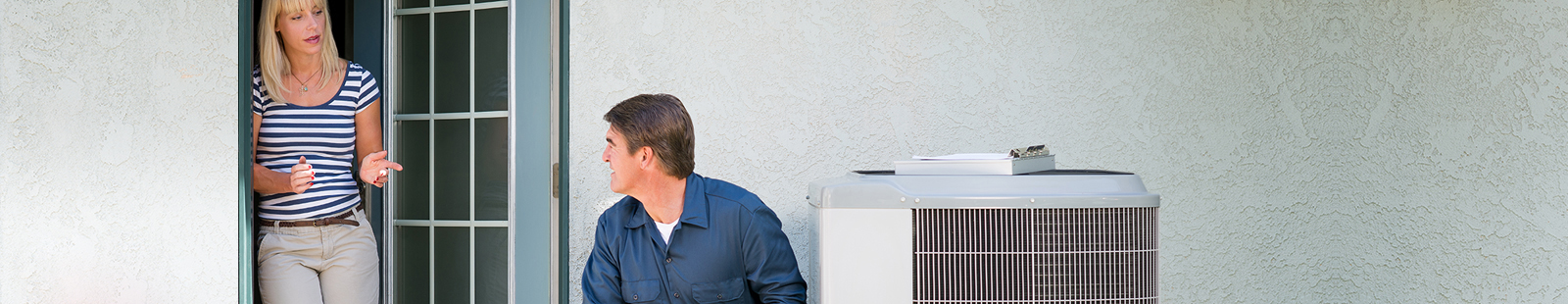 Woman talking to technician outside near air conditioner unit