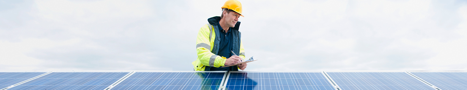Worker with clipboard checking solar panels