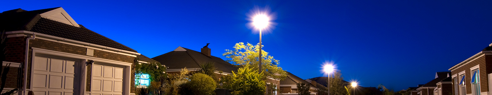Street view of homes at night with streetlamps
