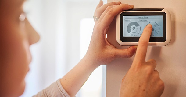 Woman touching her smart thermostat and reading how her energy consumption has gone down