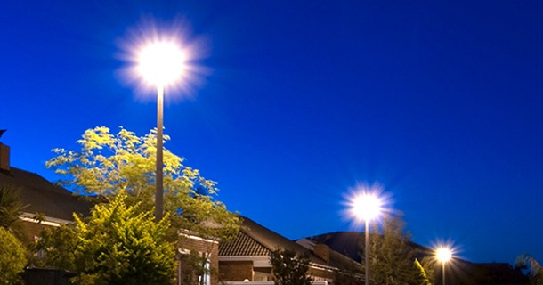 Three lamp posts lit bright in the night of a neighborhood